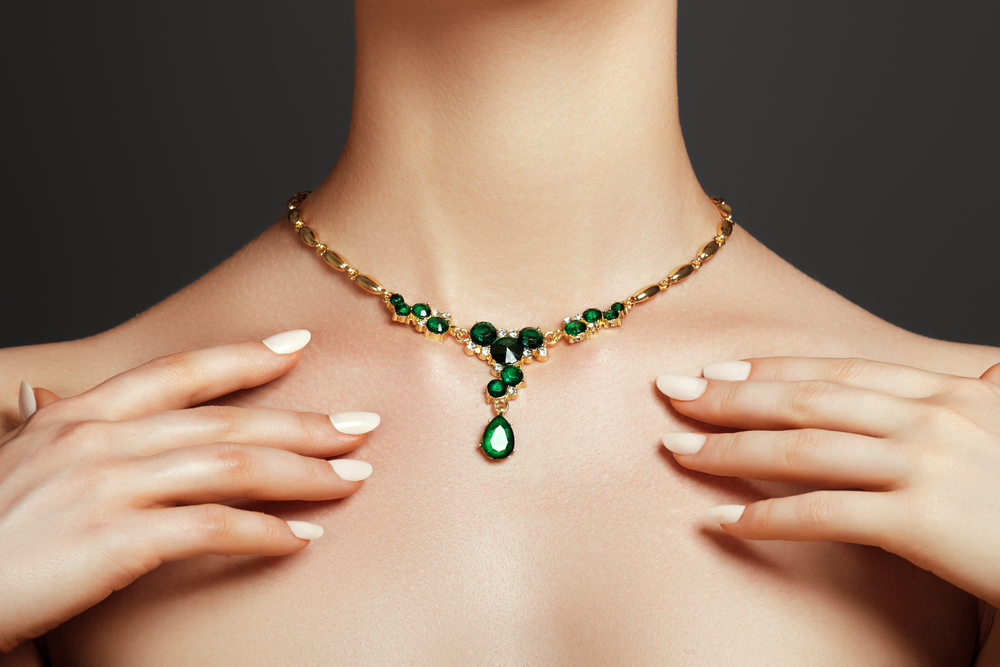 Elegant fashionable woman with jewelry. Beautiful woman with a emerald necklace. Beauty young model with a diamond pendant on a gray background. Jewellery and accessories.