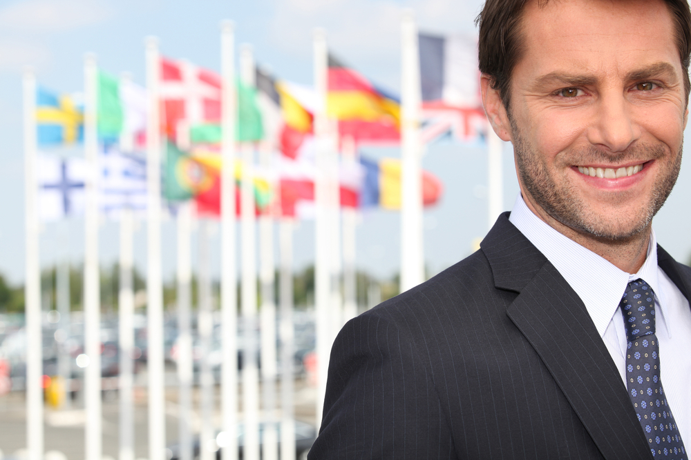 Smiling male executive in front of various flags (Bordeaux airport, France)